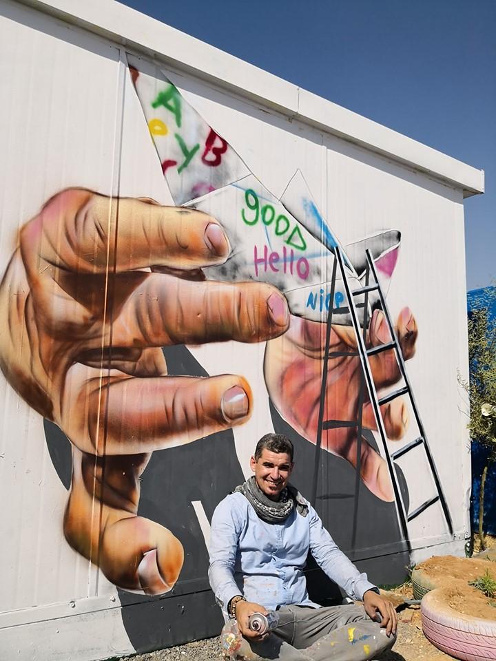 أحد فناني مخيم الزعتري يحول جدران المخيم إلى لوحات فنية مفعمة بالحياة