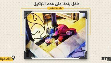 طفل يتدفأ على فحم الأراكيل أمام أحد المقاهي في مدينة اللاذقية