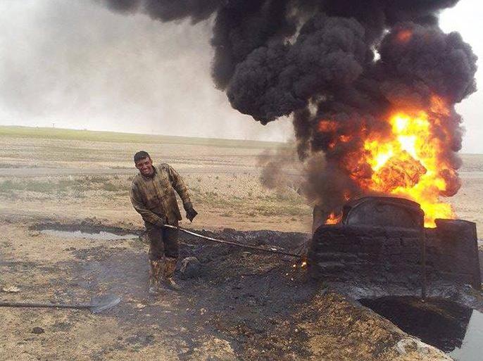 عامل في أحد حراقات النفط قي سوريا والدخان الناتج عنها