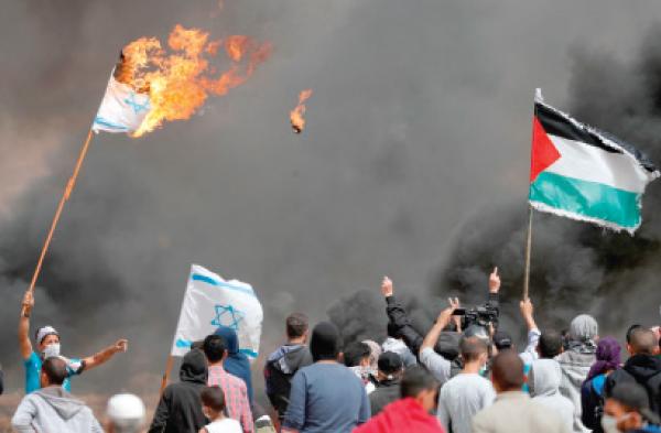 فلسطينيون يرفعون العلم الفلسطيني ويحرقون العلم الإسرائيلي خلال مسيرات العودة في غزة ارشيفية. ا ف ب